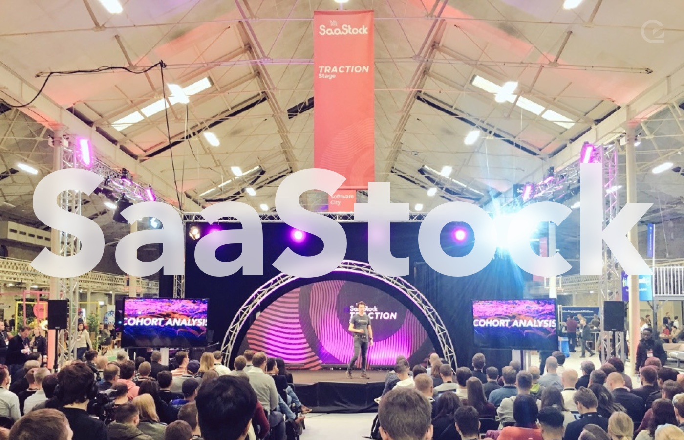 photo of James giving a talk to a crowd with SaaStock written over the photo