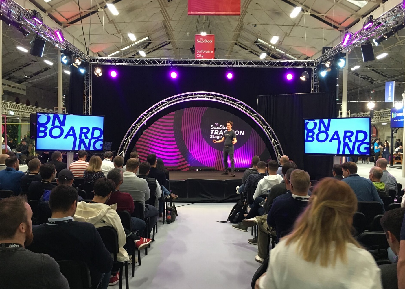 photo of James giving a talk to a crowd, there are two screens on stage that both say ONBOARDING