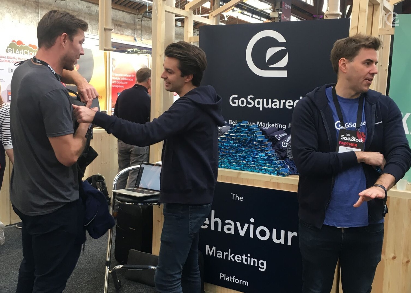 James and Russell at the GoSquared stand with rice Krispy squares talking to another vendor
