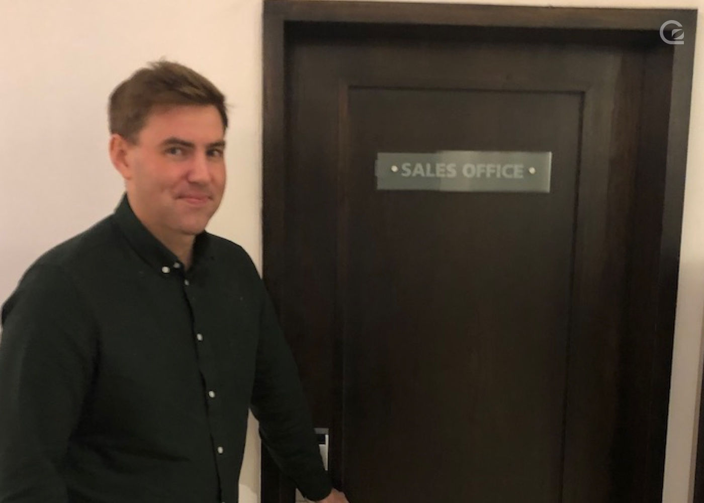 photo of Russell standing next to a door that has a sign on it reading